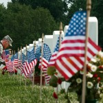 """US Army Lt. Col Brandon Robbins, a member of the 3rd US Infantry Regiment, """"The Old Guard"""" , places a flag at the foot of a US military member's gravestone in Arlington National Cemetery's Section 60, where many of the US Iraq and Afghanistan casualities are buried, May 27, 2010. The placing of the flags is part of the traditions celebrated for the Memorial Day national holiday.   AFP Photo/Paul J. Richards (Photo credit should read PAUL J. RICHARDS/AFP/Getty Images)"""