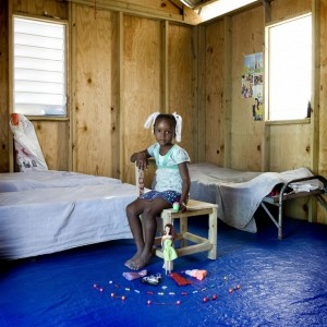 Bethsaida was born in Port-au-Prince where she has always lived in a house with her family since, almost 2 years ago, a big earthquake distroyed it. Her parents are both deaf but fortunately she's not. Now they live in a camp site out of the city. The camp was built from an american NGO which works with deaf, so in the camps almost 90% of the people can't hear and talk. All the toys that Bethsaida has are donated from the NGO. She wants to be a hairdresser and loves combing her doll to practice, but unfortunately her brother has cut off half of the hair of the doll.
