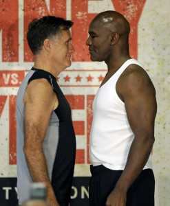 In this Thursday, May 14, 2015, photo, former Republican presidential candidate Mitt Romney, left, and five-time heavyweight boxing champion Evander Holyfield face each other during an official weigh-in, in Holladay, Utah. Romney and Holyfield are set to square off at a charity fight on Friday, May 15, in Salt Lake City. The black-tie event will raise money for the Utah-based organization CharityVision, which helps doctors in developing countries perform surgeries to restore vision in people with curable blindness. (AP Photo/Rick Bowmer)